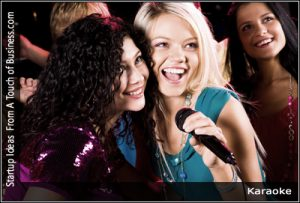 Two girls a t party singing into a microphone