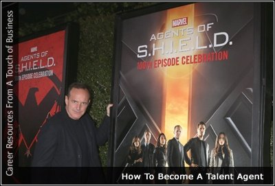 Image of Phil Coulson (Clark Gregg) standing in front of an Agents for Shield poster