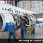 Image of Two men working on a plane engine