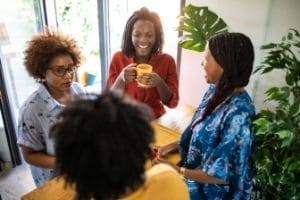 A group of women chatting two are laughing and one looks annoyed