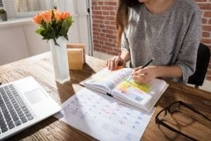 A woman sitting at a desk writing in a planner