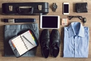 A brief case iPhone, iPad, clothing, eyeglasses, keys, and other items organized on a table